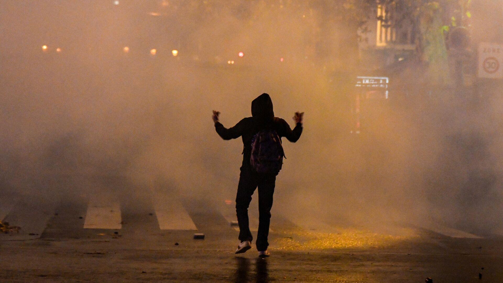 Участник акции протеста против законопроекта О глобальной безопасности в Париже - РИА Новости, 1920, 16.12.2020
