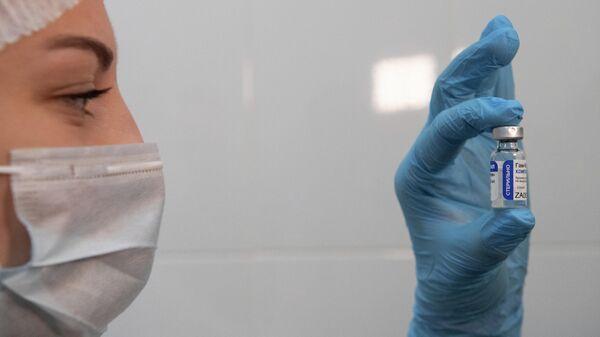 Медработник демонстрирует компонент 1 вакцины от коронавируса Спутник V