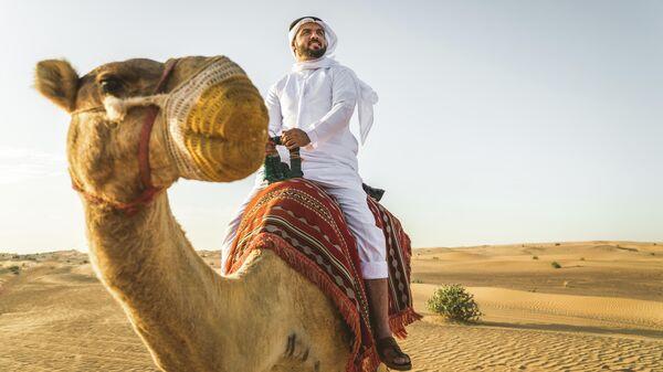Мужчина в пустыне на верблюде