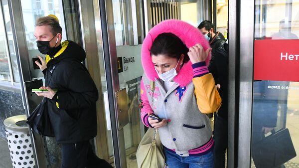 Люди в защитных масках выходят с одной из станций Московского метрополитена
