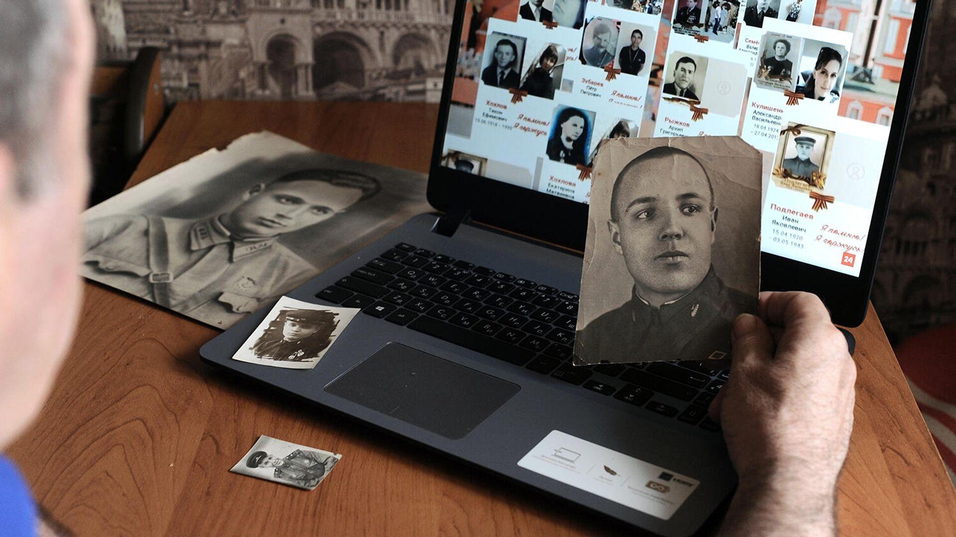 Мужчина смотрит онлайн-трансляцию акции Бессмертный полк - РИА Новости, 1920, 09.05.2021