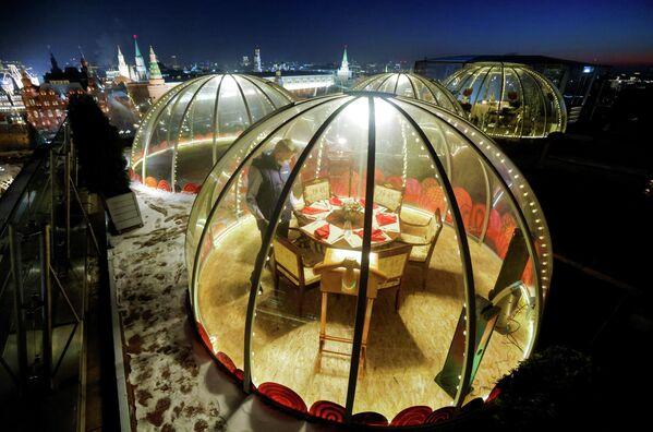 Официант накрывает стол внутри прозрачного купола на крыше отеля Ritz-Carlton в Москве, Россия