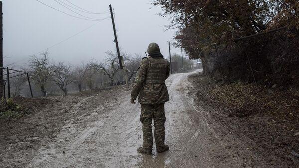 Военнослужащий армии обороны непризнанной Нагорно-Карабахской республики на одной из улиц в селе Тагавард Мартунинского района в Нагорном Карабахе