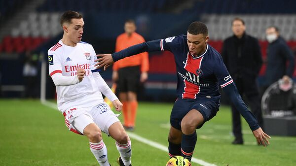Lyon's French midfielder Maxence Caqueret (L) vies with Paris Saint-Germain's French forward Kylian Mbappe (R) during the French L1 football match between Paris Saint-Germain (PSG) and Lyon (OL), on December 13, 2020 at the Parc des Princes stadium in Paris. (Photo by FRANCK FIFE / AFP)