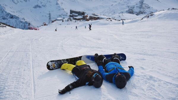 Сноубордисты на снегу в Поляне Азау, на горнолыжном курорте Эльбрус в Кабардино-Балкарской республике