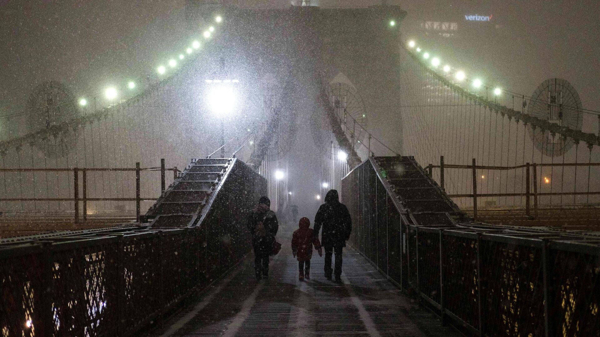 Семья идет по Бруклинскому мосту во время снегопада в Нью-Йорке - РИА Новости, 1920, 07.02.2021