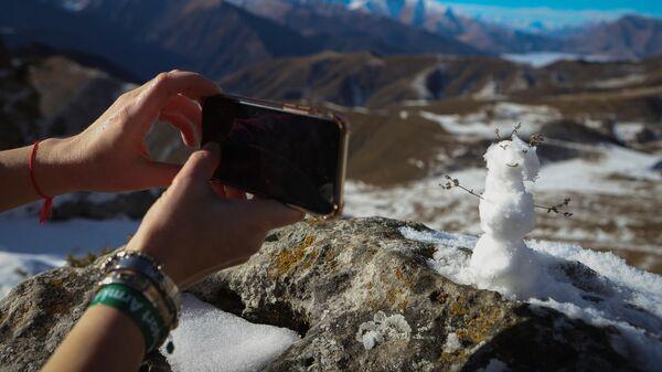 Девушка фотографирует снеговика
