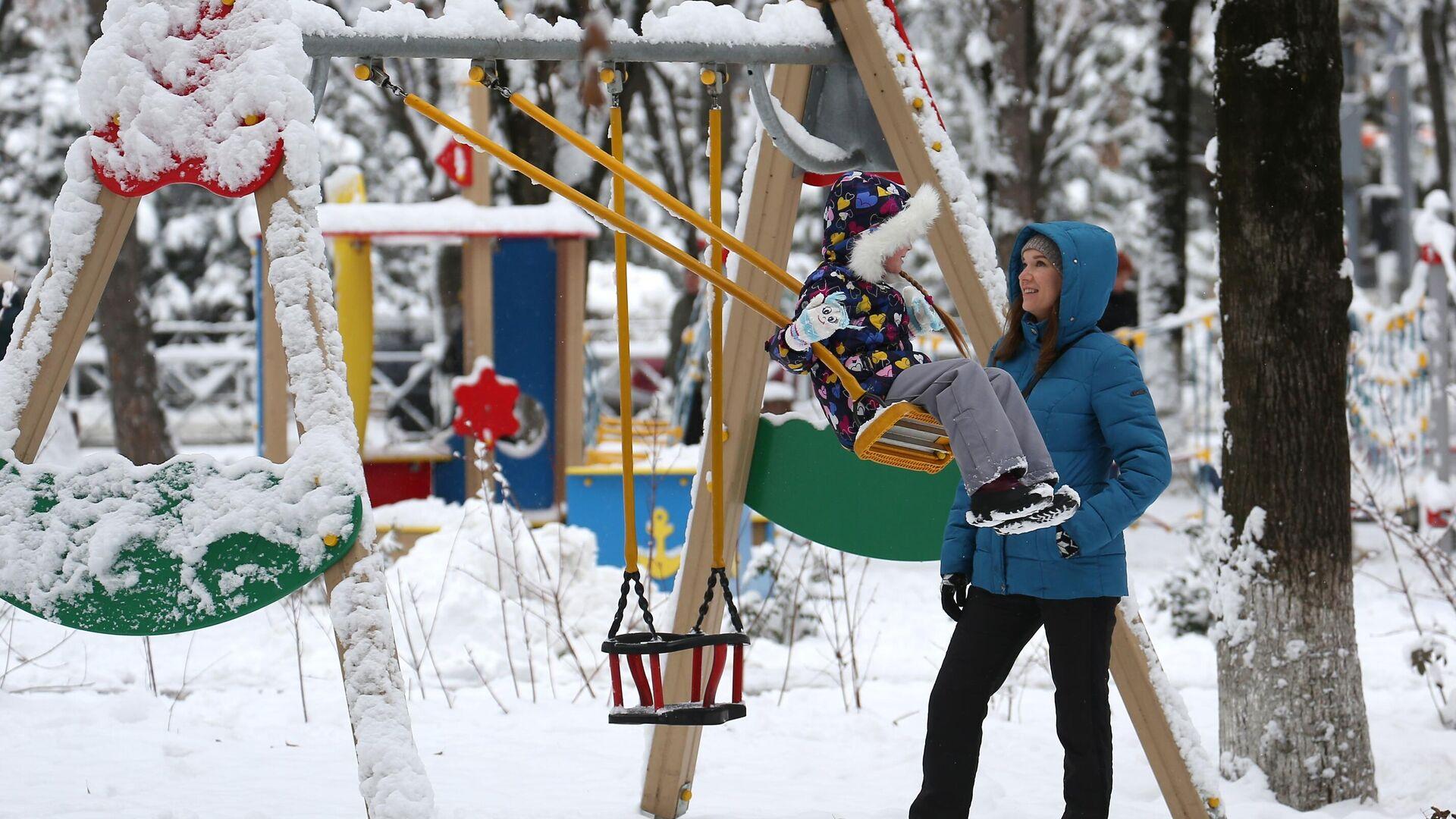 Женщина с ребенком на детской площадке Фестивального сквера в Краснодаре после снегопада - РИА Новости, 1920, 05.03.2021