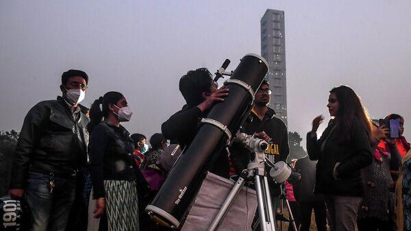 Люди наблюдают в телескоп за встречей Юпитера и Сатурна в районе Майдана в Калькутте