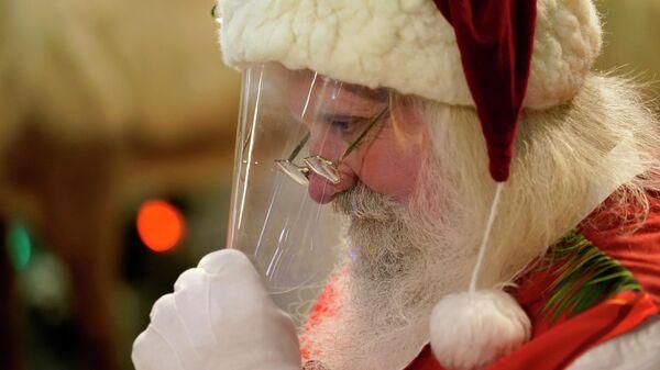 Мужчина в костюме Санта-Клауса во время посещения детей в Майами, США