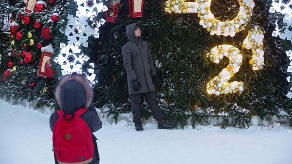Мужчина возле новогодней ели в Новосибирске