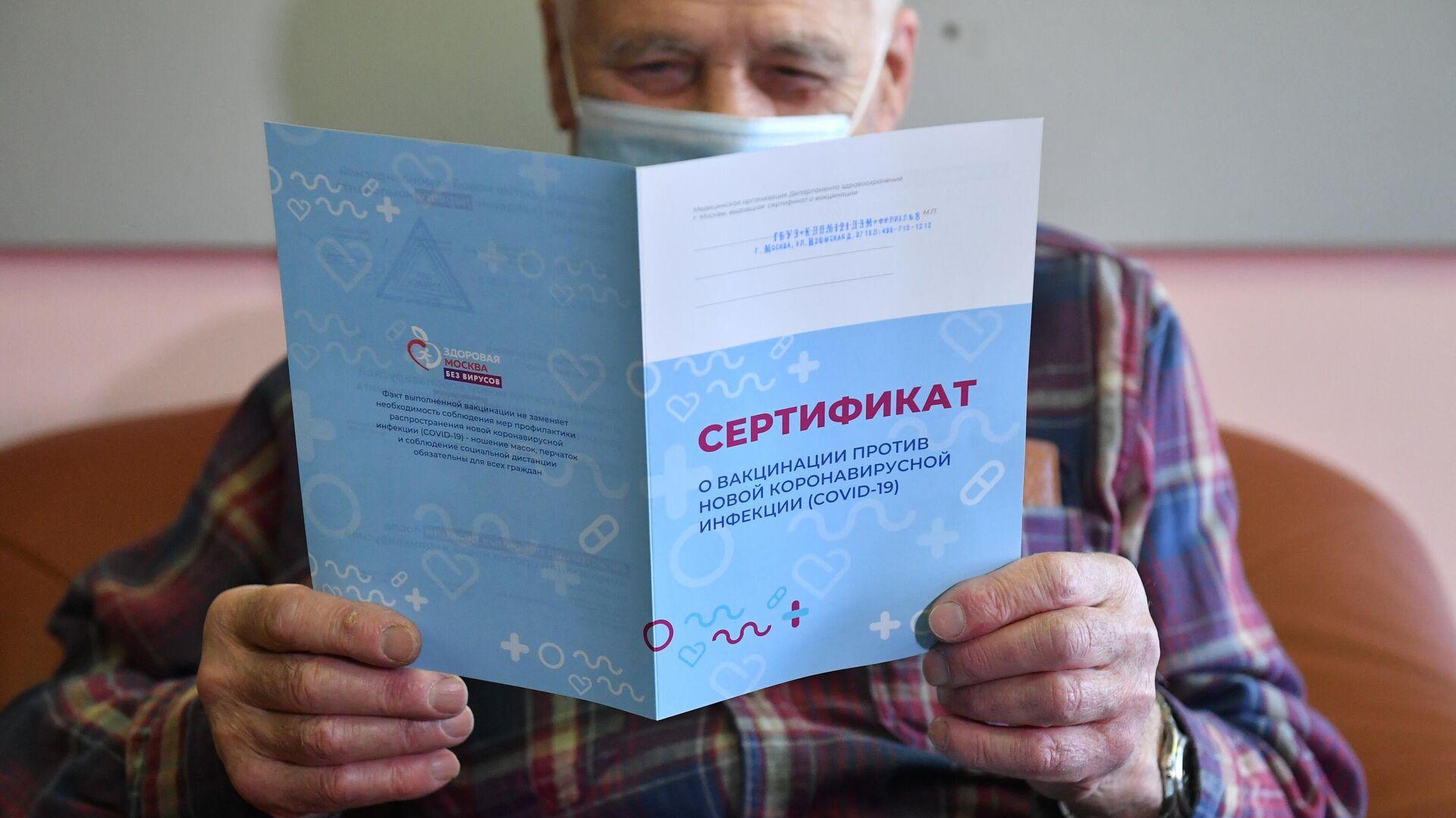 Мужчина держит в руках сертификат о вакцинации против коронавирусной инфекции (COVID-19) - РИА Новости, 1920, 31.12.2020