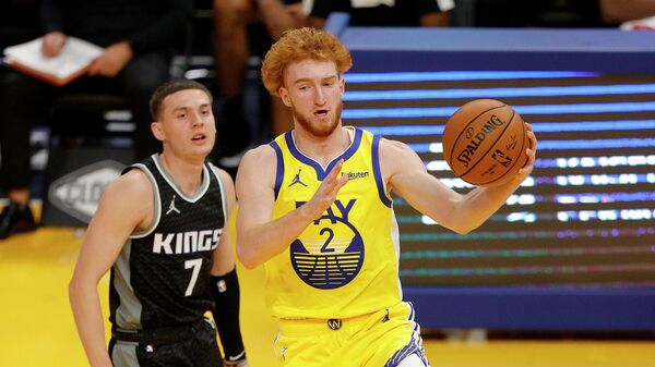 SAN FRANCISCO, CALIFORNIA - JANUARY 04: Nico Mannion #2 of the Golden State Warriors dribbles past Kyle Guy #7 of the Sacramento Kings at Chase Center on January 04, 2021 in San Francisco, California. NOTE TO USER: User expressly acknowledges and agrees that, by downloading and or using this photograph, User is consenting to the terms and conditions of the Getty Images License Agreement.   Ezra Shaw/Getty Images/AFP