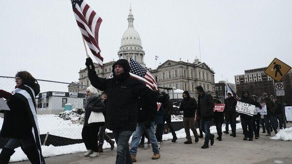 Участники акции протеста сторонников действующего президента США Дональда Трампа у здания Капитолия в Лансинге, штат Мичиган
