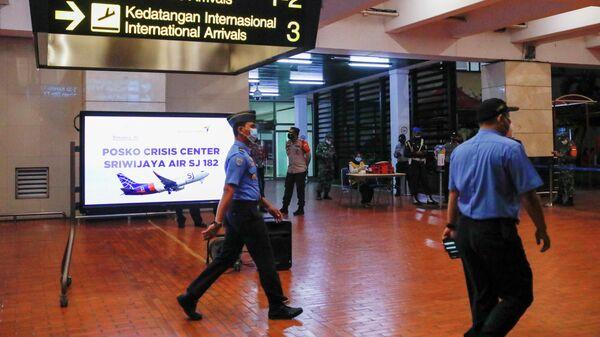 Сотрудники рядом с кризисным центром, организованным в аэропорту Джакарты, после крушения самолета компании Sriwijaya Air