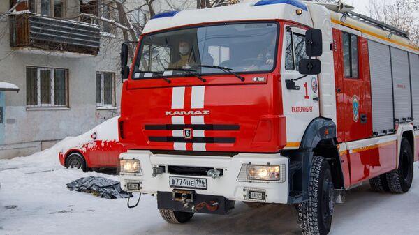 Автомобиль пожарной службы по дворе жилого дома на улице Рассветной в Екатеринбурге, где произошел пожар