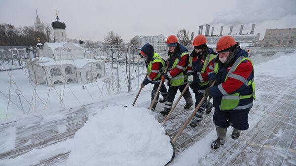 Сотрудники ГБУ Гормост проводят чистку снега и наледи на Парящем мосту в парке Зарядье в Москве