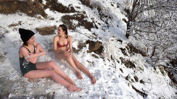Девушки обтираются снегом возле горячего сероводородного источника в Пятигорске