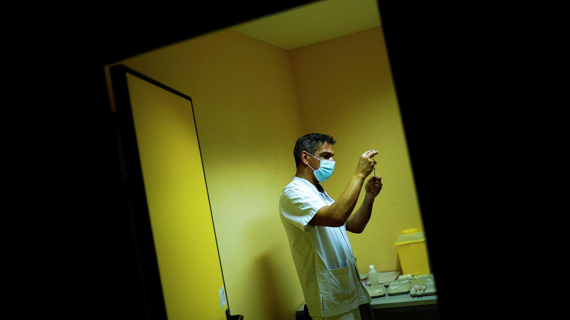 Медбрат готовит шприцы с вакцинами Pfizer / Biontech во время  вакцинации в Бельгии - РИА Новости, 1920, 01.02.2021