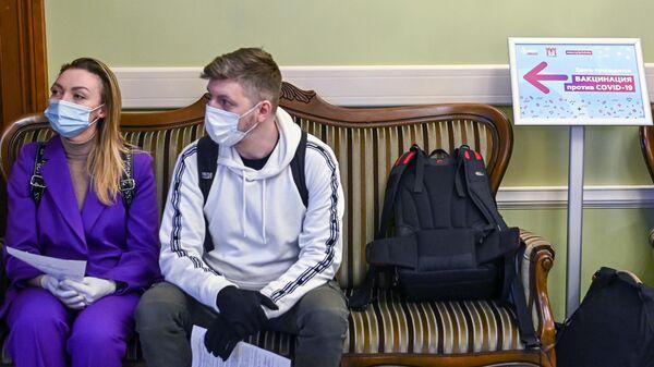 Люди в очереди на прививку от коронавируса в пункте вакцинации, открывшемся в театре Геликон-Опера, в Москве