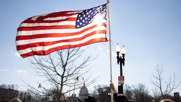 Американский флаг возле здания Капитолия США во время инаугурации избранного президента Джо Байдена
