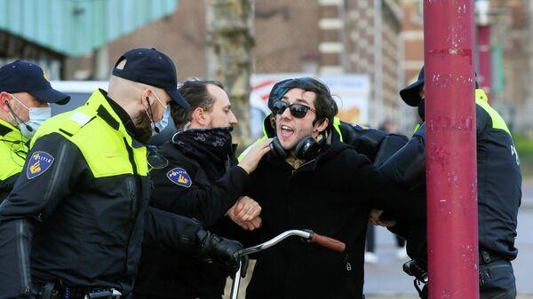 Полицейские во время задержания участника акции протеста против ограничений, введенных для сдерживания распространения коронавируса в Амстердаме