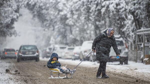Женщина переходит дорогу в Бишкеке