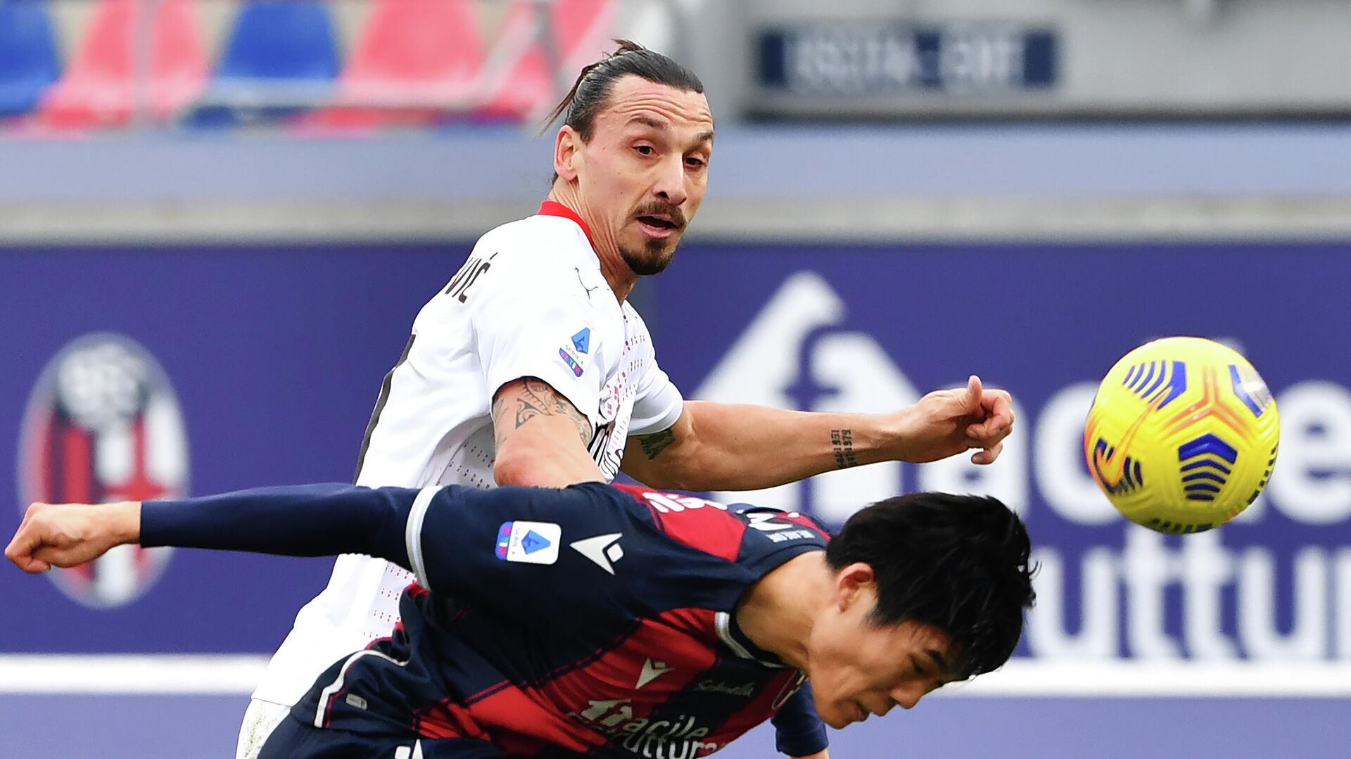 Bologna's Japanese defender Takehiro Tomiyasu (R) heads the ball past AC Milan's Swedish forward Zlatan Ibrahimovic during the Serie A football match between Bologna and AC Milan on January 30, 2021 at the Dall'Ara stadium in Bologna. (Photo by Alberto PIZZOLI / AFP) - РИА Новости, 1920, 30.01.2021