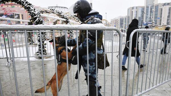 Сотрудник правоохранительных органов с собакой перед началом несанкционированной акции