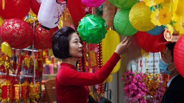 Девушка на рынке новогодних сувениров, украшений для дома и красочных цветов на центральной улице Ханоя