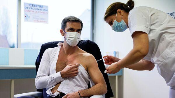 Министр здравоохранения Франции Оливье Веран получает прививку от коронавируса вакциной AstraZeneca-Oxford