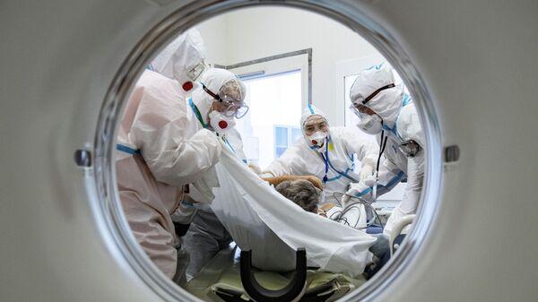 Медики помещают пациента в аппарат компьютерной томографии в городской клинической больнице №40 в Москве