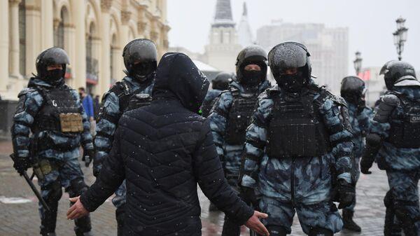Мужчина разговаривает с сотрудниками правоохранительных органов во время несанкционированной акции в Москве