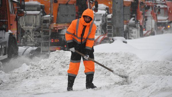 Сотрудник коммунальной службы убирает снег на улице в Москве во время снегопада.
