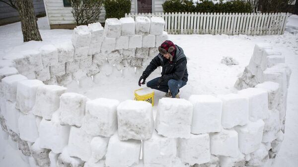Мужчина строит иглу из снега после снегопада в Огайо, США