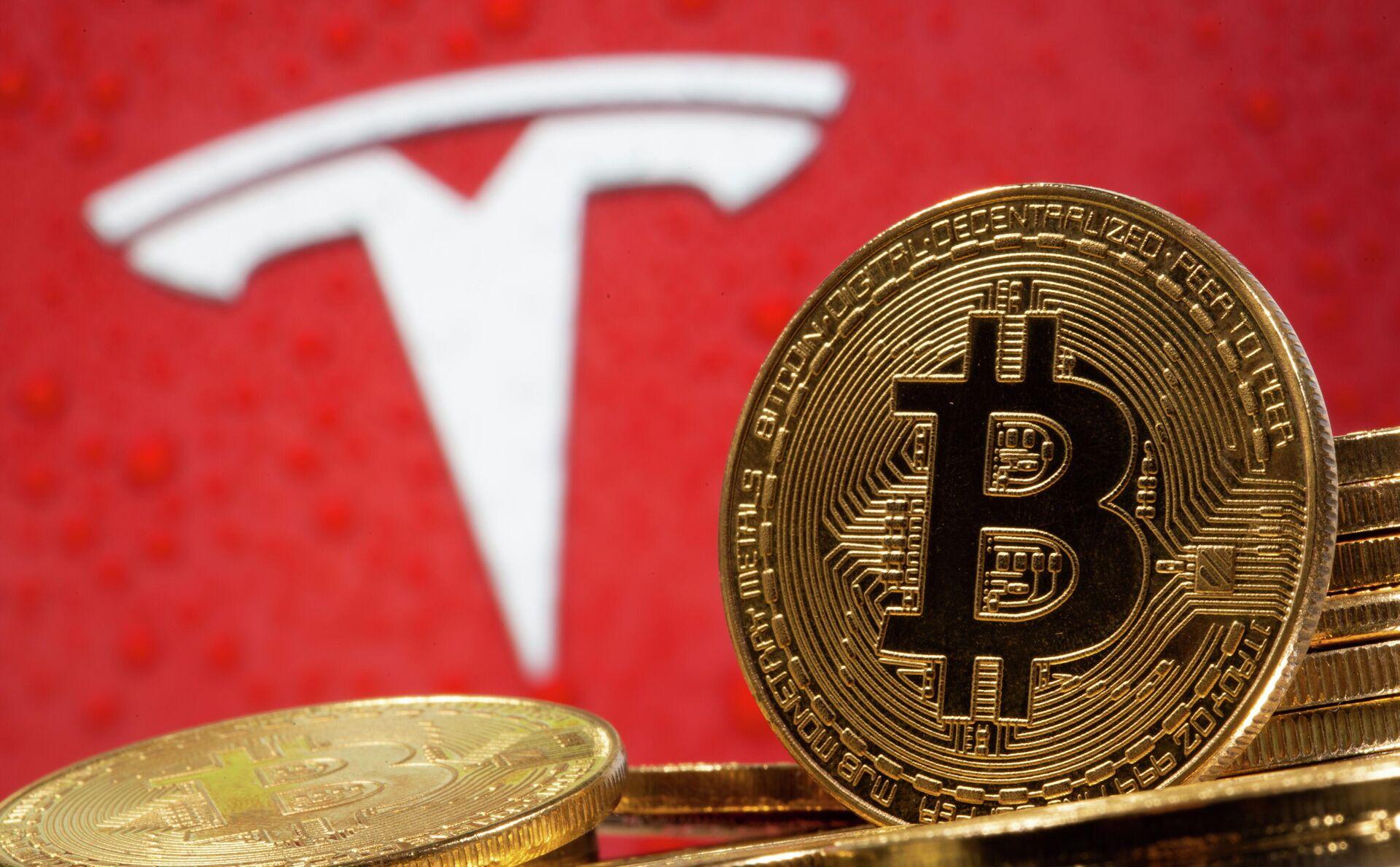 Криптовалюта биткоин на фоне иллюстрации с логотипом Tesla - РИА Новости, 1920, 24.02.2021