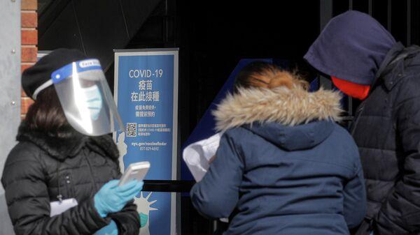 Медицинский работник помогает людям записываться на прием для получения вакцины против коронавируса (COVID-19) в Нью-Йорке, США
