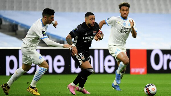 Lyon's Dutch forward Memphis Depay (C) fights for the ball during the French L1 football match between Olympique de Marseille (OM) and Olympique Lyonnais (OL) at the Velodrome stadium in Marseille on February 28, 2021. (Photo by CLEMENT MAHOUDEAU / AFP)