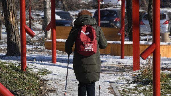 Женщина занимается скандинавской ходьбой в сквере на Океанском проспекте во Владивостоке