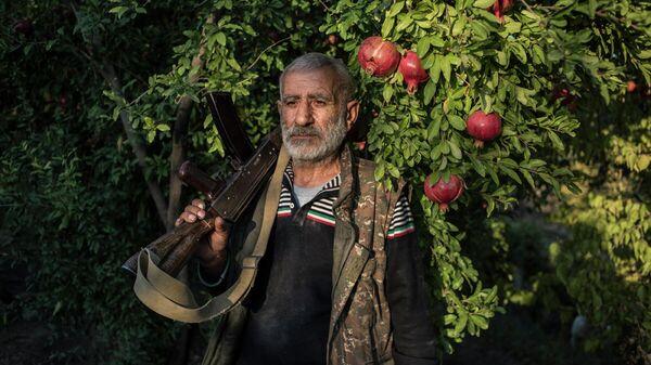 Местный житель Анушаван стоит в гранатовом саду во дворе своего дома. В его руке старый автомат Калашникова, который остался у него с первой карабахской войны. Село Ухтасар