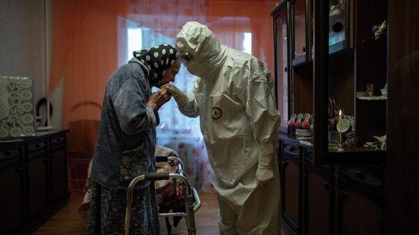 Священник отец Иоанн навещает 81-летнюю Анну Одинокову, страдающую от Covid-19, в ее доме в Москве, Россия