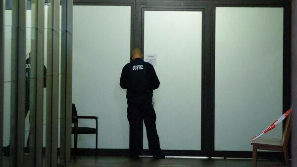 Сотрудник службы безопасности суда перед началом процесса по делу об убийстве гражданина Грузии в парке Тиргартен