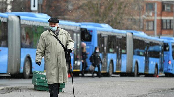 Пожилой мужчина на остановке бесплатных автобусов КМ у станции метро Беляево