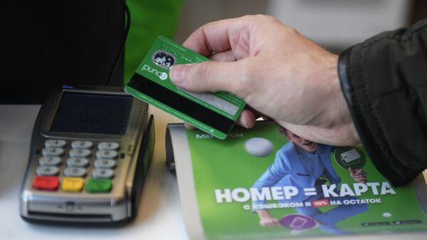 Посетитель расплачивается банковской картой в салоне сотовой связи