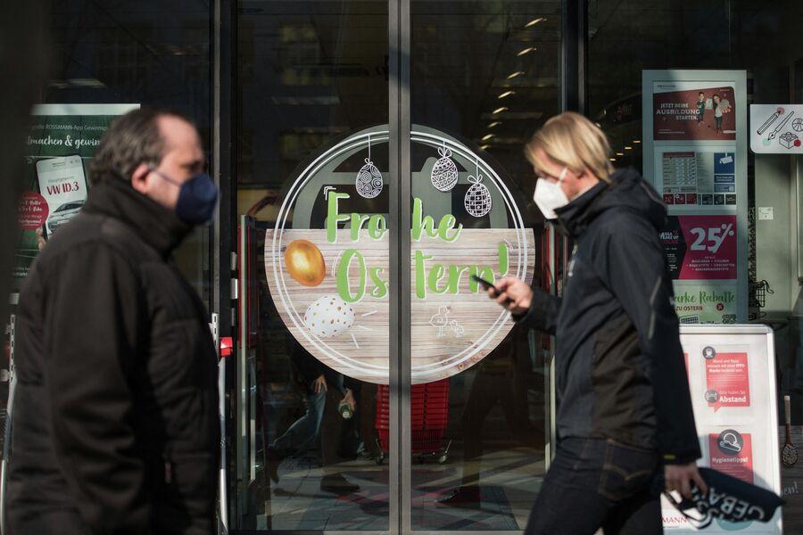 Люди проходят мимо продуктового магазина в Берлине