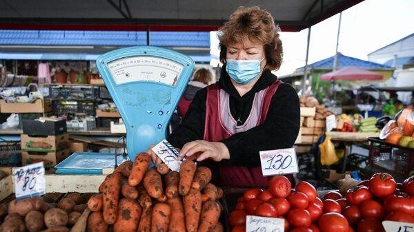 Продавец за прилавком с овощами на рынке в Симферополе