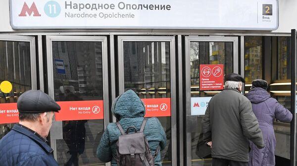 Люди заходят в вестибюль станции Народное ополчение Большой кольцевой линии московского метрополитена