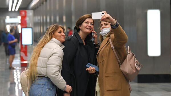 Девушки фотографируются на станции Народное ополчение Большой кольцевой линии московского метрополитена