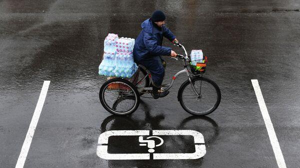 Мужчина на велосипеде везет упаковки с бутилированной водой по улице Москвы
