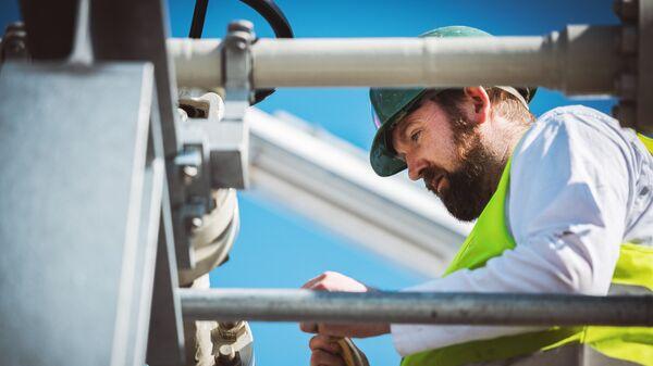 Специалист работает на территории газораспределительного центра магистрального газопровода Северный поток-2 в городе Любмин в Германии